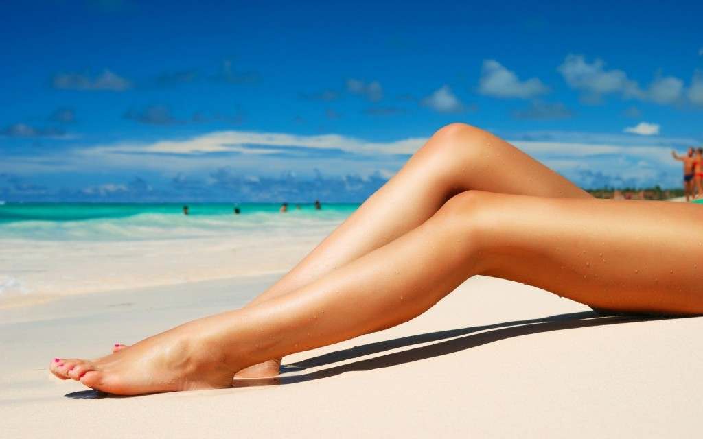 woman's smooth legs on beach after vein treatment
